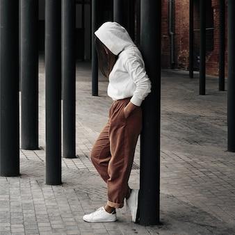 Девушка позирует на улице возле черных колонн. прогулки и развлечения по городу.
