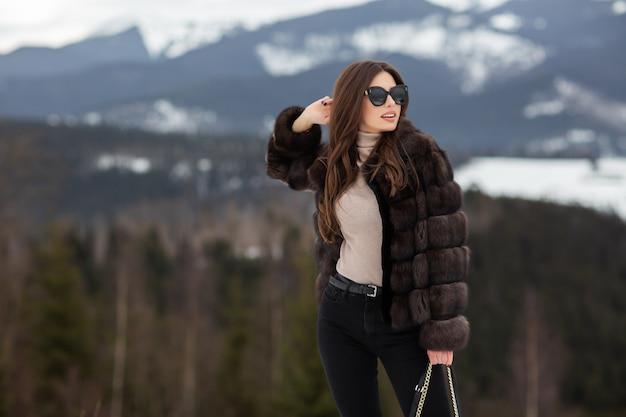 Девушка позирует на зимних горах