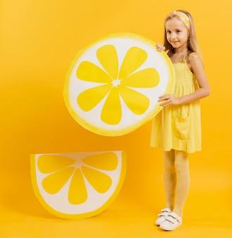Девушка позирует, держа украшение ломтик лимона