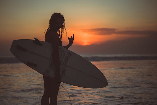 Girl posing with a board at sunset