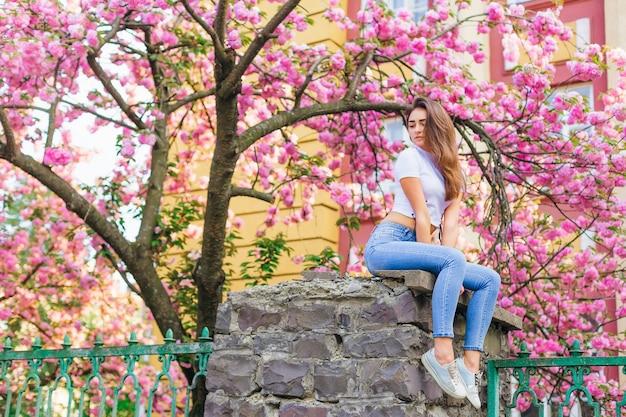 外の枝の花でポーズをとる女の子