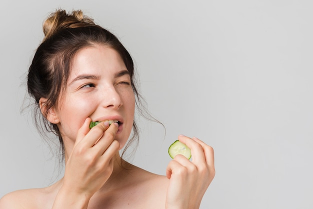 Girl posing with cucumber slices