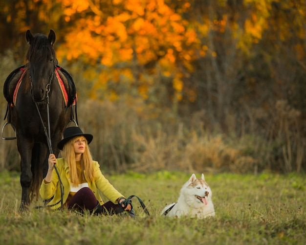 Girl posing with a horse and a dog