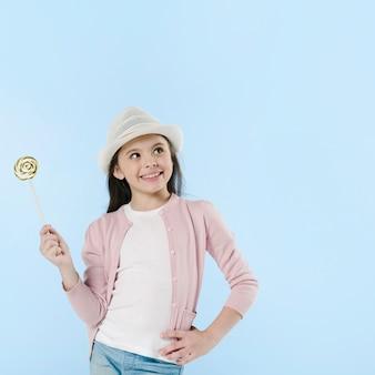 Girl posing with lollipop in studio