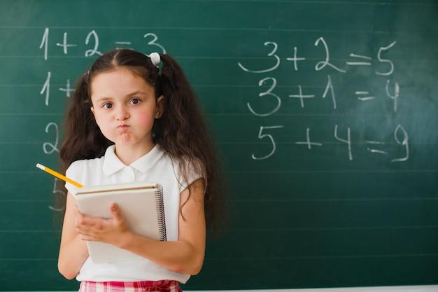 Девушка позирует с блокнотом в математическом классе