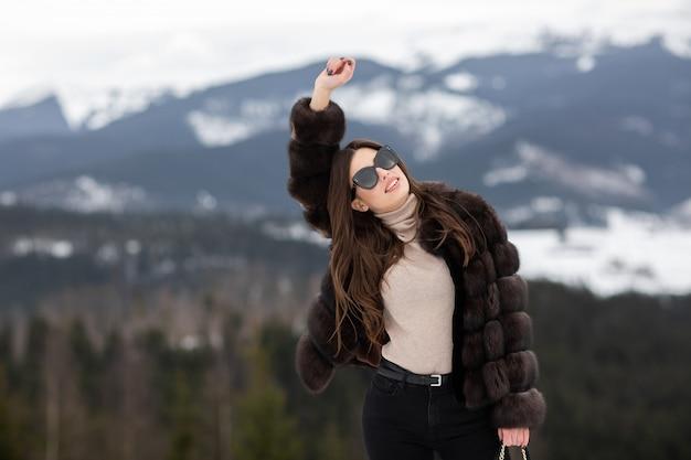 Девушка позирует с поднятой рукой в горах зимой