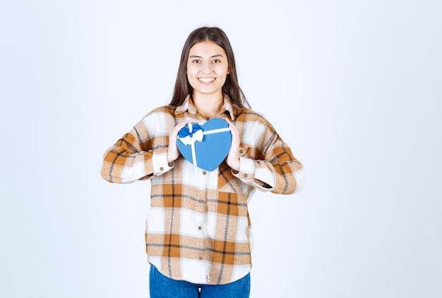 白い壁にサプライズギフトでポーズをとる女の子。
