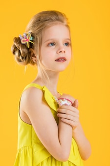 Girl posing on yellow background.