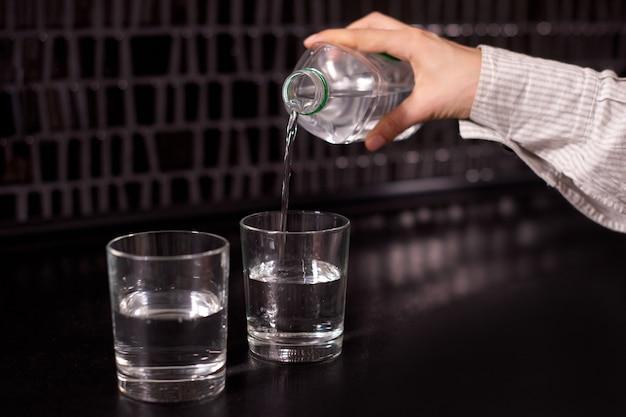 黒いテーブルの上の2つのグラスにきれいな水を注ぐ女の子