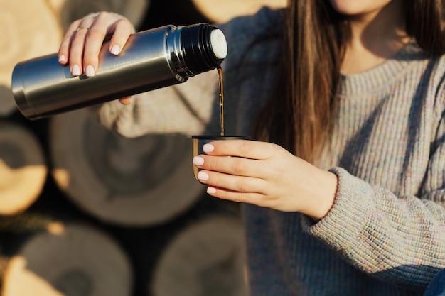 森のハイキング中に魔法瓶から熱い飲み物を注ぐ女の子