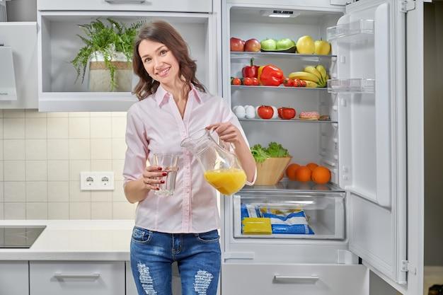 Девушка наливает сок в стакан