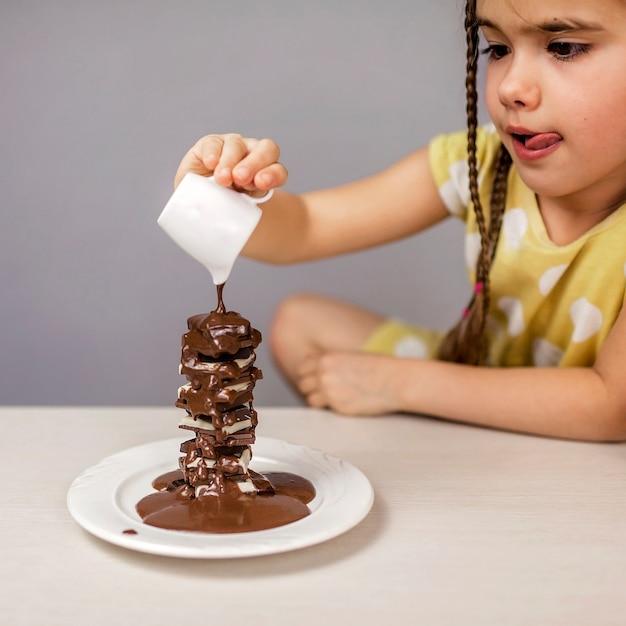 다른 초콜릿 조각 더미에 액체 핫 초콜릿을 붓는 소녀