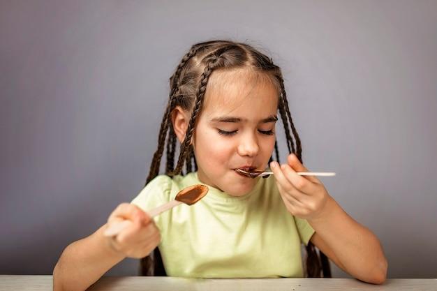 티스푼으로 액체 핫 초콜릿을 붓는 소녀, 초콜릿이 많지 않습니다.