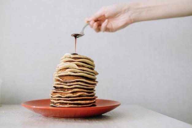 Девушка наливает ложку вишневого варенья на стопку блинов домашний вкусный завтрак из настоящей еды