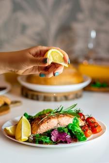 Девушка наливает рыбу с лимонным соком. только лимон с красной рыбой. стейк из лосося на гриле. стейк из лосося с листьями салата, помидорами черри и дольками лимона. еда на обед. жареная красная рыба. приготовление лосося в духовке