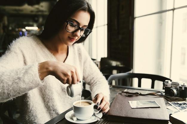 Девушка наливает молоко в чашку кофе
