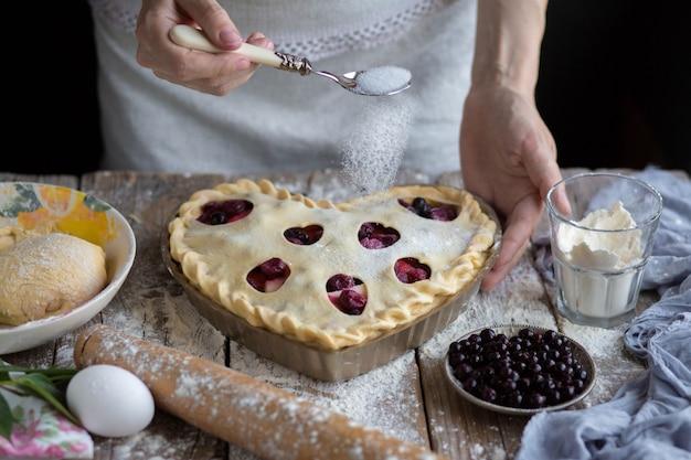 Девушка наливает сахар для выпечки. сахар посыпать фруктовым пирогом. приготовить в домашних условиях.