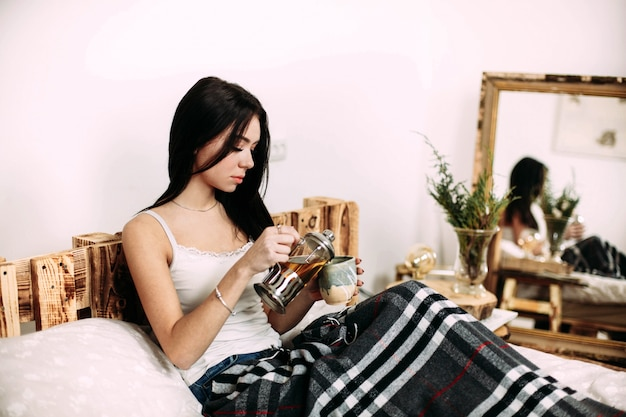 Girl pours tea in a cup lying under black plaid