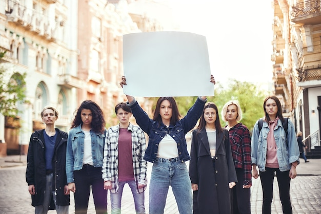 Girl power group of young women standing on the road during protest march young woman