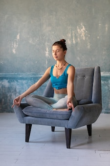 Girl practice yoga while sitting on armchair with lotos pose crossed legs.