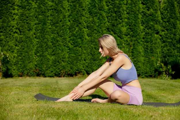 Girl practices yoga in the backyard of her house in summer