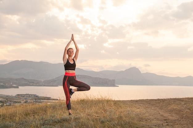 소녀는 바다에 산에서 요가를 연습합니다.