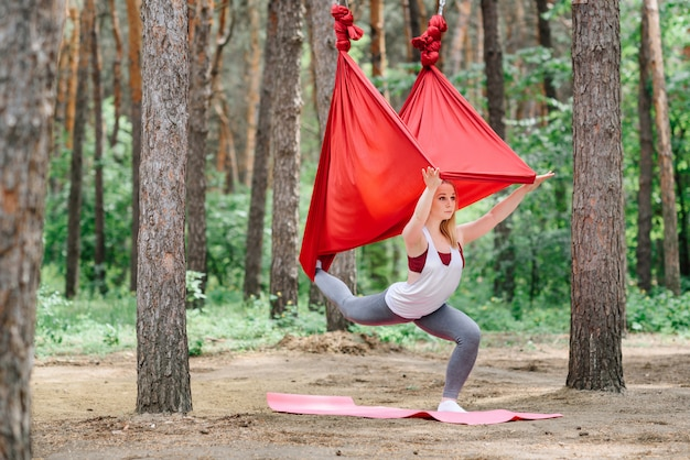 The girl practices yoga with a hammock in nature.
