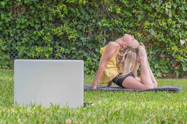 家で体操を練習して、ラップトップでオンラインビデオを見ている女の子。
