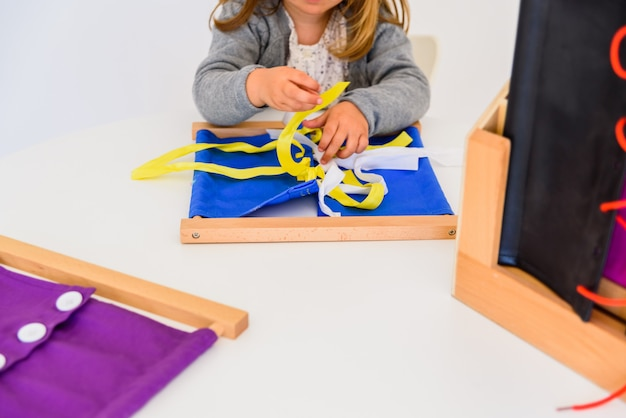 Girl practicing how to tie ties in a wooden frame.