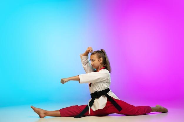 Ragazza che pratica taekwondo con cintura nera isolata su parete sfumata