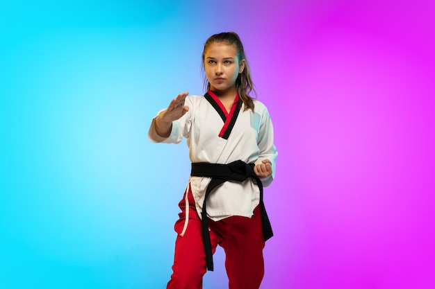 グラデーションの壁に分離された黒帯でテコンドーを練習している女の子