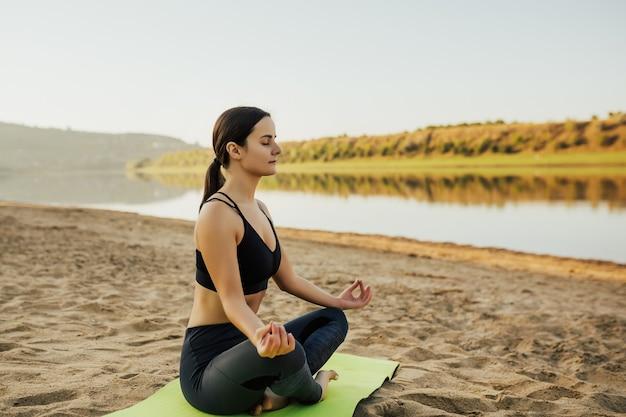 화창한 아침에 해변에서 로터스 위치에서 요가와 명상을 연습하는 소녀.