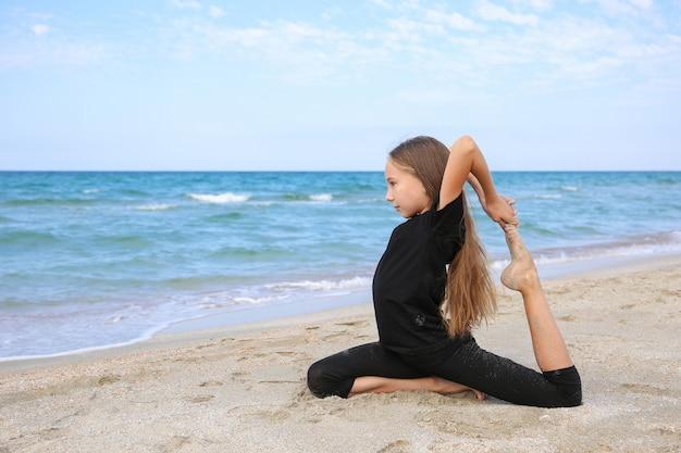 Girl practicing yoga on beach.