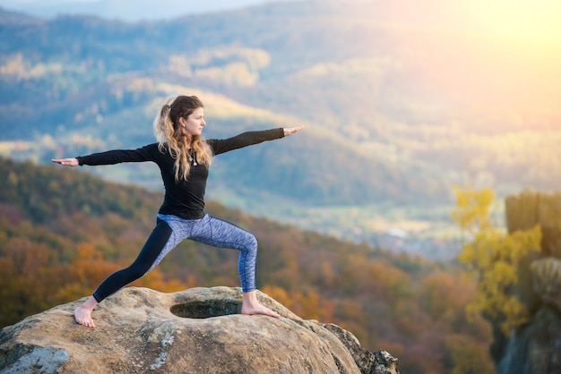 Girl practicing yoga, doing asana on the top of the mountain