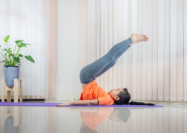 Girl practicing yoga at home