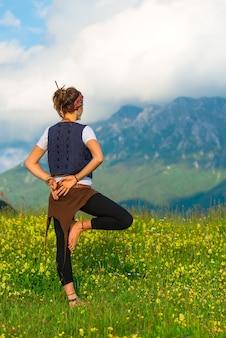 山の中で自然の中でヨガを練習している女の子