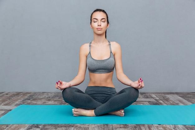 Девушка упражнениями йоги, изолированные на сером фоне