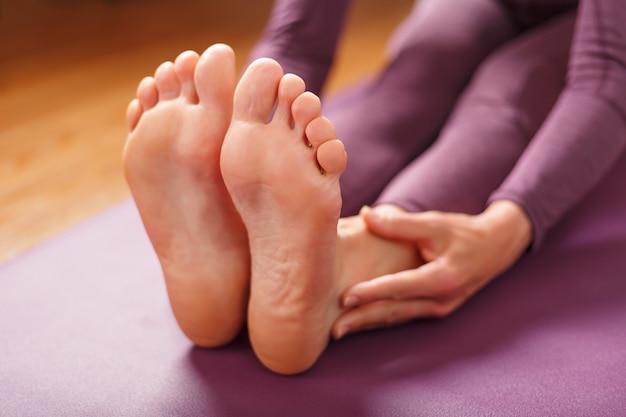 Girl practicing yoga leaning forward sitting, feet forward-paschimottanasana pose, training on a lilac mat