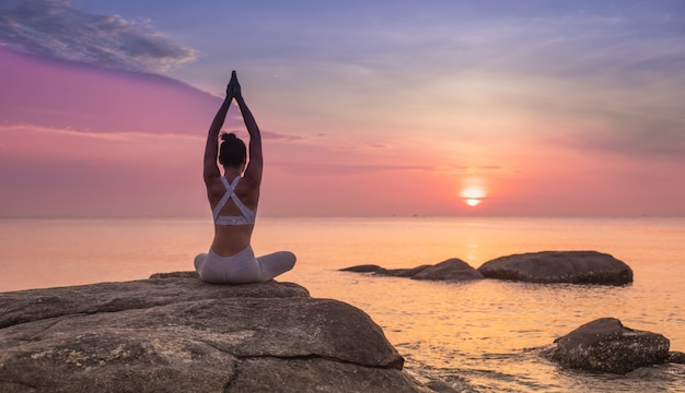 Девушка практикуя йогу на утесе