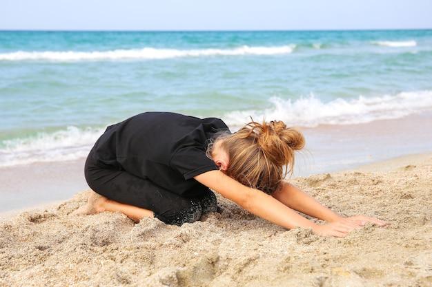 Девушка упражнениями йоги на пляже.