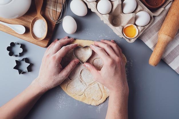 女の子は、灰色の背景にハートの形をした、平らな敷設の構成でクッキーを準備します。女性の手にクッキーカッターと生地。バレンタインデー、父の日、母の日の食べ物の概念。