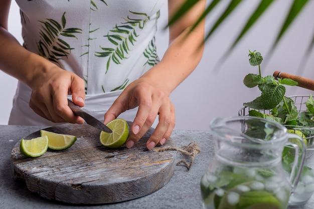 Girl prepares summer lemonade cuts lemon fresh drink