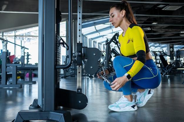 ジムでの運動のためにケーブル クロスオーバー マシンを準備する女の子
