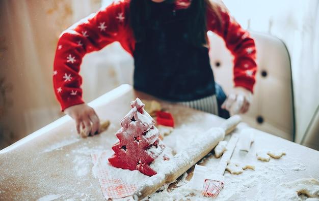Девушка готовит еду на рождественские праздники, используя много муки на столе, в одежде санта-клауса