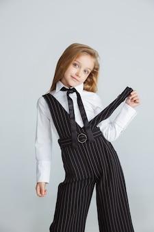 긴 여름 방학 후 학교를 준비하는 소녀. 학교로 돌아가다. 흰색 스튜디오 배경에 학교 유니폼 포즈 작은 여성 백인 모델. 어린 시절, 교육, 휴일 개념.