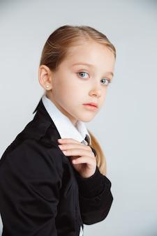 긴 여름 방학 후 학교를 준비하는 소녀. 학교로 돌아가다. 흰 벽에 학교의 제복을 입은 작은 여성 백인 모델 포즈. 어린 시절, 교육, 휴일 개념.