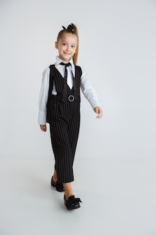 긴 여름 방학 후 학교를 준비하는 소녀. 학교로 돌아가다. 흰색 배경에 배낭 학교 유니폼 포즈 작은 여성 백인 모델. 어린 시절, 교육, 휴일 개념.