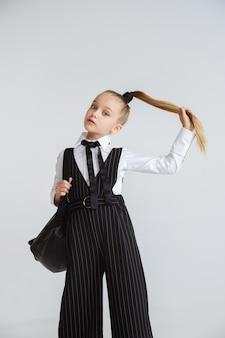 長い夏休みの後に学校の準備をしている女の子。学校に戻る。白い壁にバックパックで学校の制服を着てポーズをとる小さな女性の白人モデル。子供の頃、教育、休日の概念。