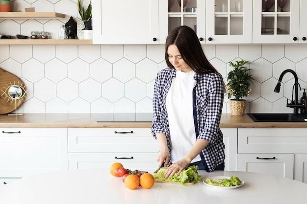 Girl preparing fresh salad in the kitchen