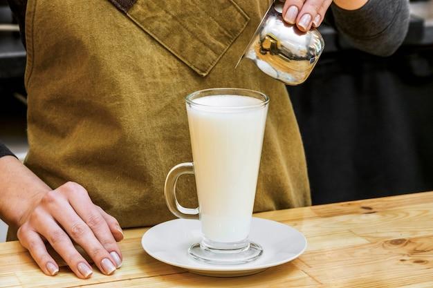 Girl preparing glass of coffee